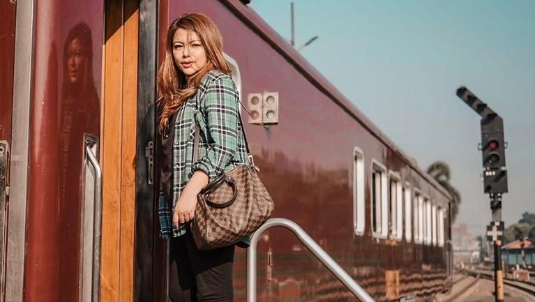 Mengenakan baju hitam yang dipadukan dengan kemeja hijau, Wina siap pergi naik kereta priority.
