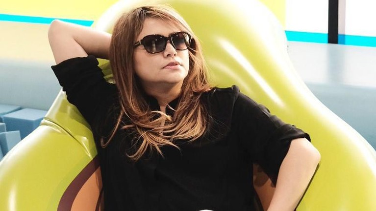 Pose santai Wina Natalia saat duduk di atas air bag dengan kacamata hitamnya. Kecantikan Wina kerap dipuji netizen.