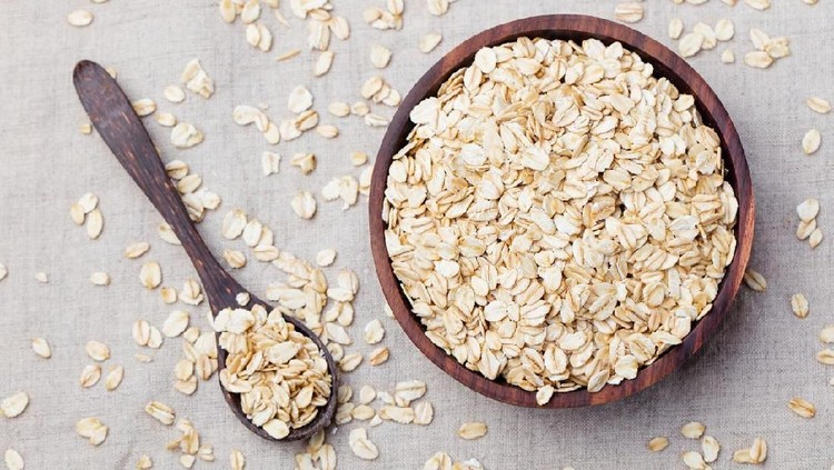 Healthy breakfast Organic oat flakes in a wooden bowl Grey textile background Top view Copy space