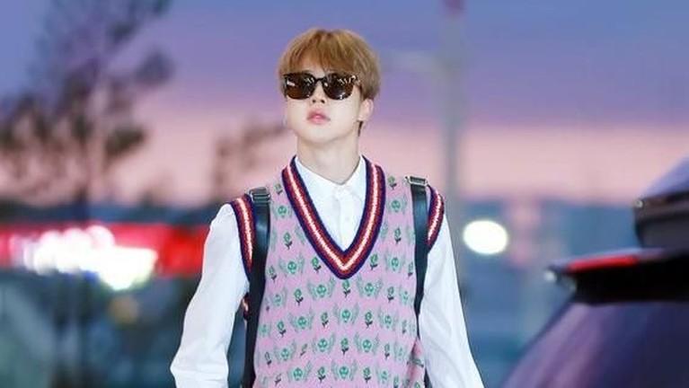 Dengan menggunakan sebuah rompi sekolah rajut merek Gucci, dipadukan dengan kemeja putih di dalamnya dan dipadukan dengan celana hitam, membuat Jimin terlihat santai namun elegan dan moderen.