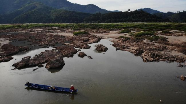 This aerial photo taken on October 31, 2019 shows a fisherman on a boat in Mekong River in Pak Chom district in the northeastern Thai province of Loei. - The once mighty Mekong river has been reduced to a thin, grubby neck of water across northern Thailand - record lows blamed on drought and a recently opened dam hundreds of kilometres upstream in Laos. (Photo by Lillian SUWANRUMPHA / AFP)