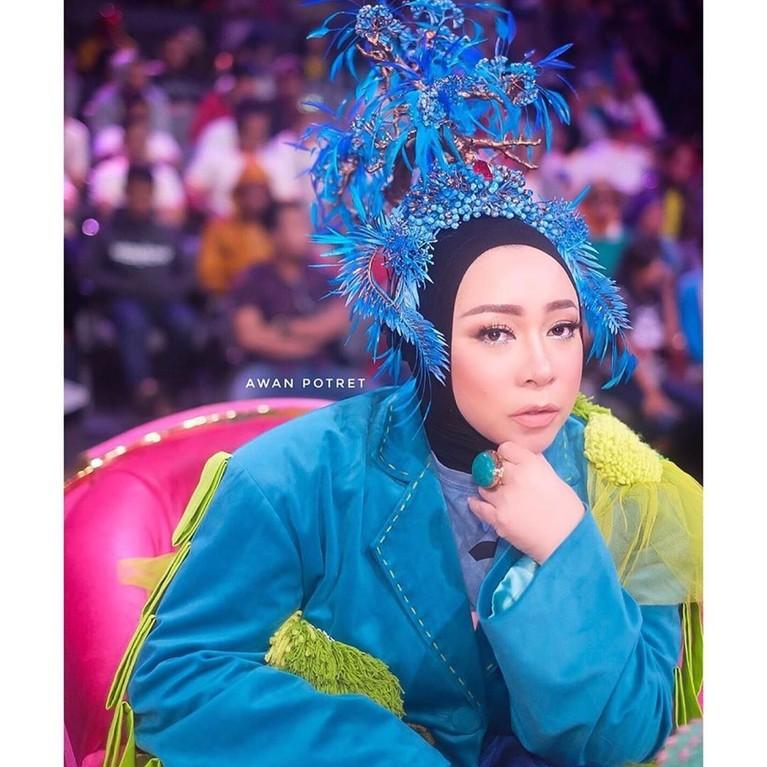 Melly Goeslaw penyanyi dan pencipta lagu yang nampak percaya diri mengenakan pakaian berwarna cerah dan mermotif unik yang dipadukan dengan headpiece yang tak kalah nyentrik.