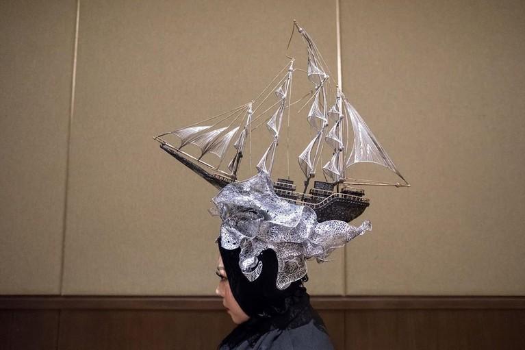 Melly pernah mengenakan hiasan kepala berbentuk kapal layar karya Rinaldy Yunardi.