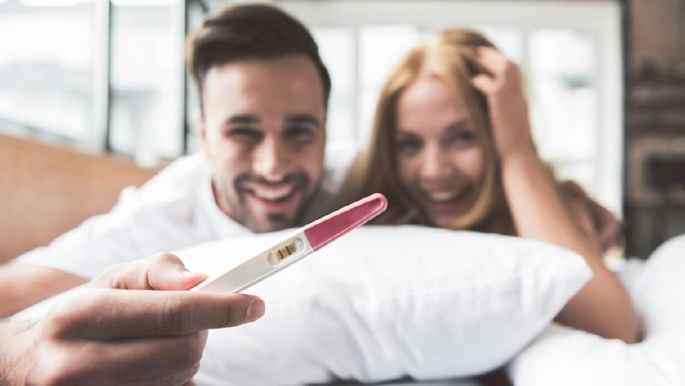 We are pregnant. Excited young man and woman are hugging and smiling. Focus on two strips on pregnancy test stick in male hand