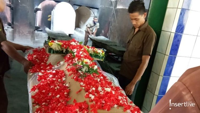 Peti kayu yang berisi mendiang jenazah Suhu Naga sudahditaburi bunga dan disiapkan untuk masuk ruang kremasi.