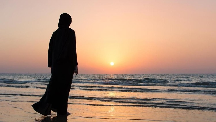 Woman in hijab standing on the beach looking at horizon