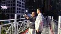 Gubernur DKI Jakarta, Anies Baswedan tampak berswafoto dengan pejalan kaki di JPO. (Foto: Anies di JPO tanpa atap (Rahel/detikcom))