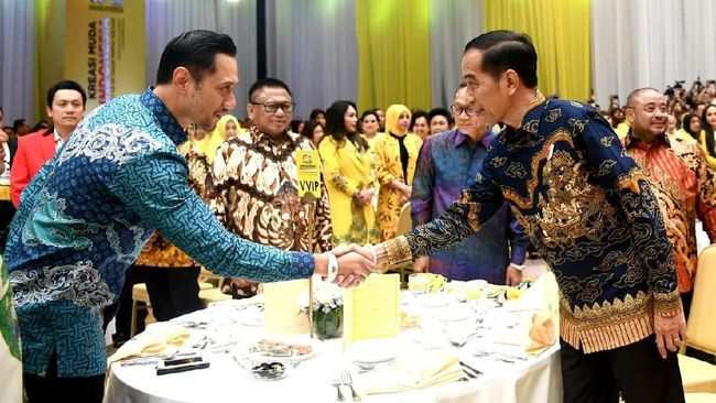 Waketum Demokrat Agus Harimurti Yudhoyono dan Presiden Jokowi bertemu HUT Golkar di Jakarta. Mereka saling bersalaman dan bertukar senyum.