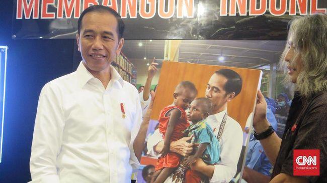 Dalam pameran foto Membangun Indonesia, Presiden Jokowi mengaku sangat terkesan dengan hasil bidikan fotografer, saat dirinya sedang menggendong dua anak Papua.