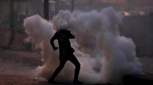 Seorang pengunjuk rasa antipemerintah dikepung gas air mata yang ditembakkan oleh pasukan keamanan Irak pada Minggu (10/11). (AP Photo/Hadi Mizban)