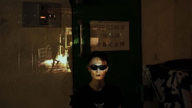 Sejumlah peserta demo di Hong Kong membuat fose foto di depan proyektor yang menampilkan gambar kerusuhan di negara mereka baru-baru ini.