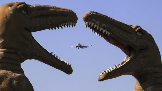 Sebuah pesawat terbang melewati patung dinosaurus di Taman 'Valley of Animals' di Chandigarh pada Sabtu (9/11). (Photo by VIJAY MATHUR / AFP)