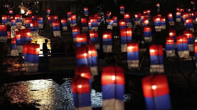 Seorang pengunjung berjalan di dekat lentera dalam Festival Lentera Seoul di sepanjang aliran Cheonggye di Seoul, Korea Selatan, Kamis (7/11).  (AP Photo/Lee Jin-man)