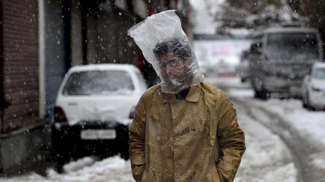 Seorang pria Kashmir menutupi kepalanya dengan kantong plastik saat salju turun di Srinagar, Kashmir pada Kamis (7/11). (AP Photo/Mukhtar Khan)