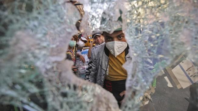 Para demosntrak Irak bentrok dengan pasukan keamanan di lapangan Khallani di Baghdad saat demonstrasi antipemerintah berlangsung pada Senin (11/11). (Photo by AHMAD AL-RUBAYE / AFP)