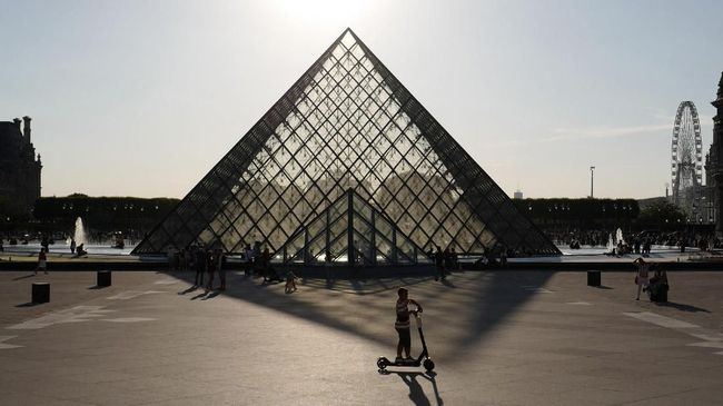 A boy rides an electric scooter in front of the Pyramid of The Louvre Museum (Pyramide du Louvre) as the sun sets in Paris on July 3, 2019. (Photo by Ludovic MARIN / AFP)