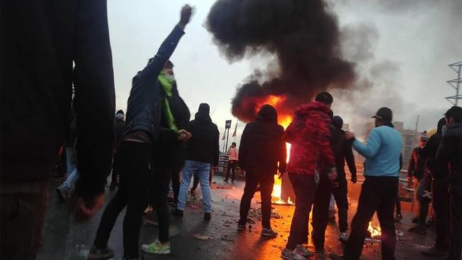 Iranian protesters gather around a fire during a demonstration against an increase in gasoline prices in the capital Tehran, on November 16, 2019. - One person was killed and others injured in protests across Iran, hours after a surprise decision to increase petrol prices by 50 percent for the first 60 litres and 300 percent for anything above that each month, and impose rationing. Authorities said the move was aimed at helping needy citizens, and expected to generate 300 trillion rials ($2.55 billion) per annum. (Photo by - / AFP)