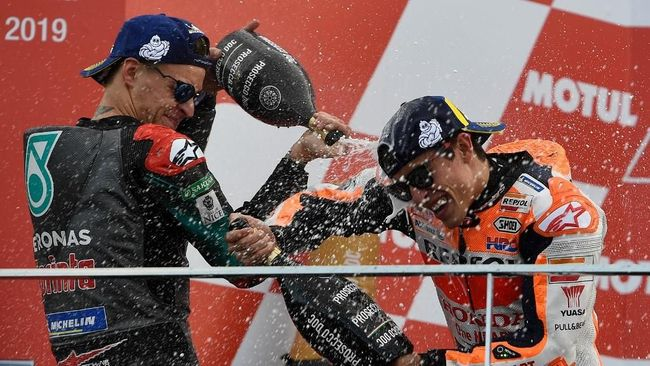 Winner Repsol Honda Team's Spanish rider Marc Marquez (R) and second placed Petronas Yamaha SRT's French rider Fabio Quartararo celebrate with champagne after the MotoGP race of the MotoGP Valencia Grand Prix at the Ricardo Tormo racetrack in Cheste near Valencia, on November 17, 2019. - World champion Marc Marquez clinched his 12th MotoGP victory of the season in final race in Valencia. (Photo by PIERRE-PHILIPPE MARCOU / AFP)