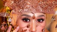 <p>Selanjutnya, Dian Pelangi tampil dengan busana pengantin khas Palembang. Lengkap dengan siger berwarna gold. Riasan wajahnya pun terlihat lebih <em>heavy</em>dan dipertegas dengan pulasan lipstik bernuansa <em>bold</em>. (Foto: Instagram @sistawedding)</p>