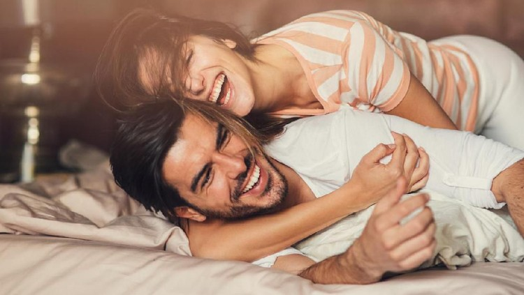 Happy young playful couple in bed.