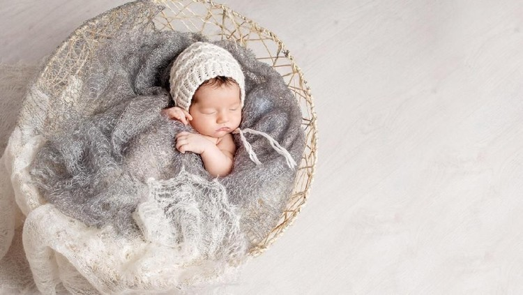 Beautiful little newborn baby 2 weeks sleeping in a basket with knitted plaid. Portrait of pretty  newborn baby. Copy space