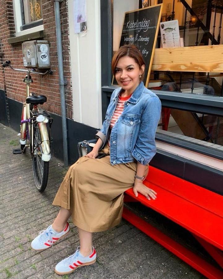 <p>Penampilan Najwa Shihab kali ini tak terlihat seperti usia 42 tahun ya, Bunda. Najwa tampak seperti anak muda dengan atasan kaus garis merah putih, jaket denim, dan rok cokelat. Gayanya semakin keren dengan sepatu sneakers berwarna putih. (Foto: Instagram @najwashihab)</p>