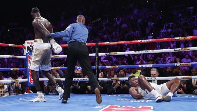 Wasit Kenny Bayless menepikan Wilder setelah memukul jatuh Ortiz. (AP Photo/John Locher)