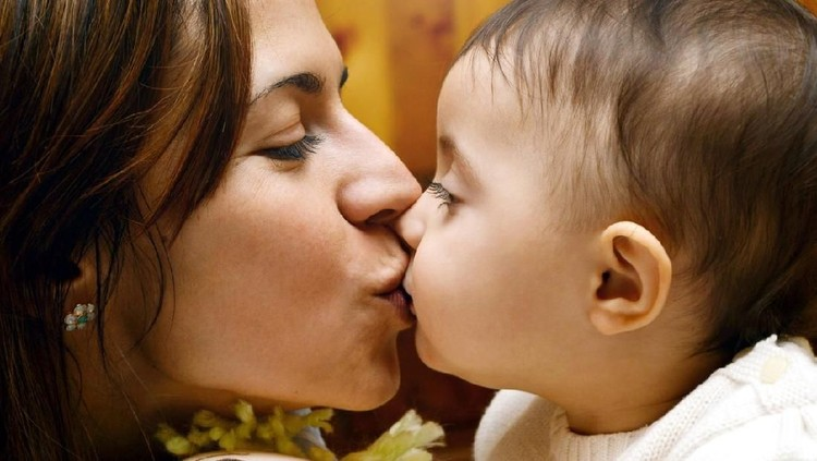 side view of mother kissing and embracing her baby girl, lifestyle shot.