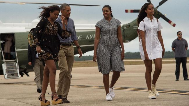 US President Barack Obama, First Lady Michelle Obama and daughters Malia and Sasha walk to board Air Force One at Cape Cod Air Force Station in Massachusetts on August 21, 2016 as they depart for Washington after a two-week holiday at nearby Martha's Vineyard. (Photo by NICHOLAS KAMM / AFP)