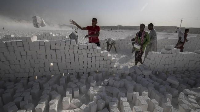 Akan tetapi, kerja keras mereka dan bayaran yang diterima tidak sebanding dengan keuntungan yang didapat dari bisnis tersebut. (Photo by Khaled DESOUKI / AFP)