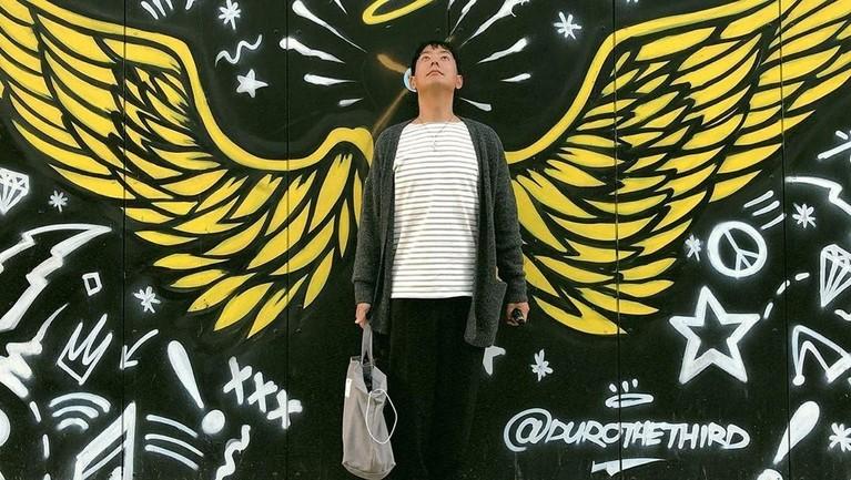 Hyung Joon mengambil potret dirinya di Toronto, Kanada, dengan latar mural berbentuk sayap kuning yang besar.