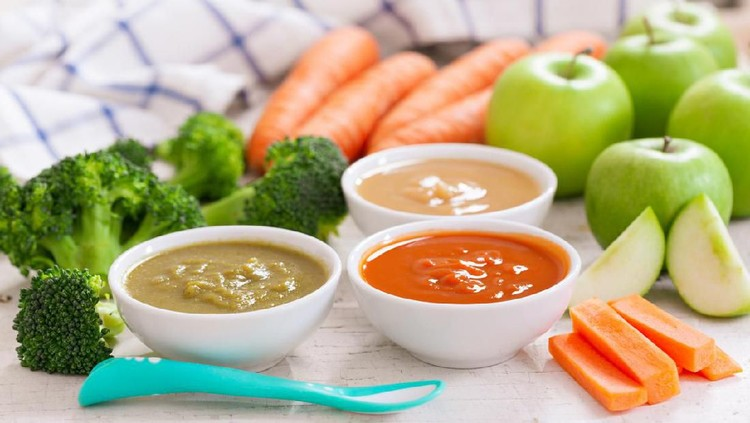 Baby food. Various bowls of fruit and vegetable puree with ingredients for cooking on wooden table