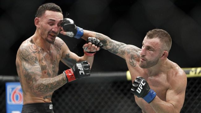 Alexander Volkanovski hits Max Holloway in a mixed martial arts featherweight championship bout at UFC 245, Saturday, Dec. 14, 2019, in Las Vegas. (AP Photo/John Locher)