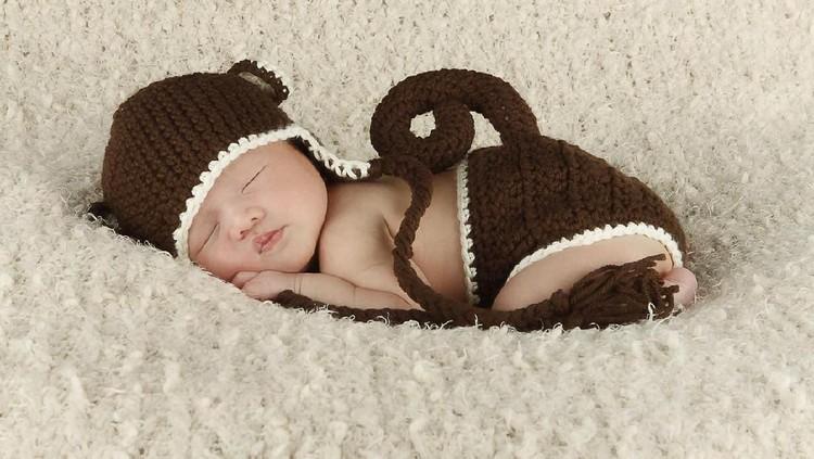 Newborn Asian baby in crochet monkey outfit.