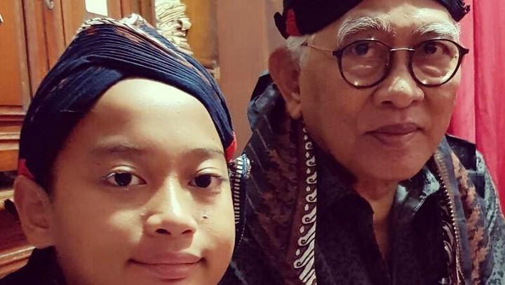 <p>Lihat saja, di foto ini Gus Mus terlihat kompak dengan cucunya menggunakan blangkon khas Jawa. Mirip enggak, Bun? (Foto: Instagram @aunyosa)</p>