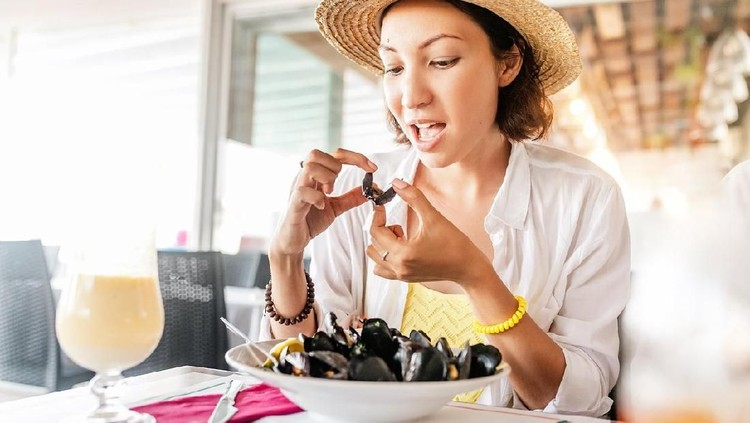 Close-up of woman eating mussel
