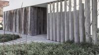 Desain sederhana namun elegan membuat rumah menyatu dengan lingkungan alaminya. Dinding-dinding kayu tampaknya muncul dari tanah sementara rumput melewati celah.