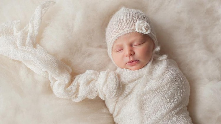 A portrait of a beautiful, seven day old newborn baby girl wearing a white, knitted, mohair bonnet. She is swaddled with a gauzy, white fabric and sleeping on cream colored wool batting.