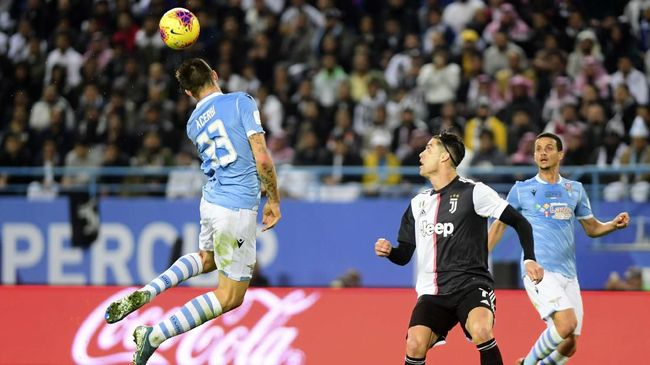Lazio's Francesco Acerbi, left, jumps to hit the ball during his team Super Cup match against Juventus at King Saud University Stadium, in Riyadh, Saudi Arabia, Sunday, Dec. 22, 2019. (AP Photo/Nasser Alharbi)