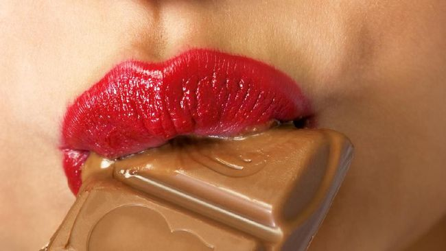 Closeup of young woman with chocolate in mouth