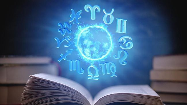 Open book on astrology on a dark background. The glowing magical globe with signs of the zodiac in the blue light. Concept of prediction and magic