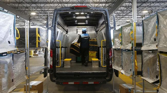 In this Dec. 17, 2019, photo An Amazon delivery driver moves stowed containers into his truck after Amazon robots deliver separated packages by zip code at an Amazon warehouse facility in Goodyear, Ariz. Doing your job side-by-side with robots isn't easy. According to their makers, the machines should take on the most mundane and physically strenuous tasks. In reality, they're also creating new forms of stress and strain in the form of injuries and just the unease of working in close quarters with mobile half-ton devices that direct themselves. (AP Photo/Ross D. Franklin)