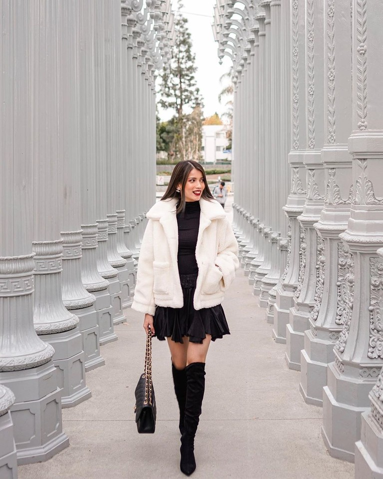 Berbeda denga gaya sebelumnya, dalam foto ini Sabrina tampak lebih feminim. Ia mengenakan mini dress hitam yang dipadukan dengan coat putih dan high boots.