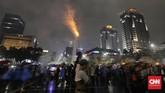 Meskipun diguyur hujan, warga tetap antusias merayakan pergantian malam tahun baru 2020 di kawasan Sudirman-Thamrin, Jakarta, Selasa, 31 Desember 2019.