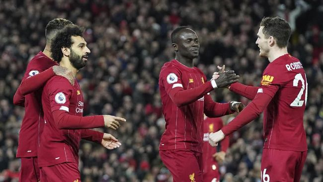 Liverpool's Mohamed Salah, front left, celebrates with teammates after scoring his side's opening goal during the English Premier League soccer match between Liverpool and Sheffield United at Anfield Stadium, Liverpool, England, Thursday, Jan. 2, 2020. (AP Photo/Jon Super)
