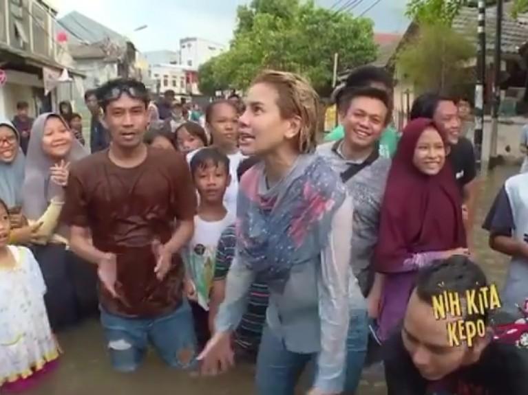 Ia tampak antusias menghibur warga yang berada di lokasi banjir.