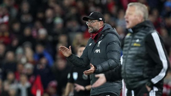 Liverpool's manager Jurgen Klopp, left, and Sheffield United's manager Chris Wilder react during the English Premier League soccer match between Liverpool and Sheffield United at Anfield Stadium, Liverpool, England, Thursday, Jan. 2, 2020. (AP Photo/Jon Super)
