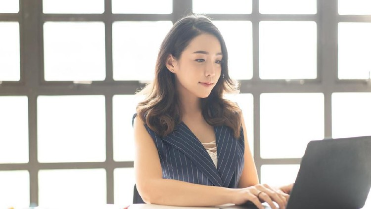 Portrait of smiling pretty young Asian business woman working on laptop in her workstation