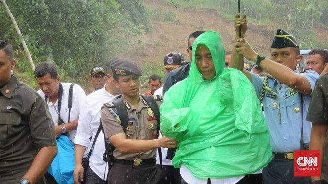 Jokowi terpaksa kembali ke kantor desa saat hendak ke titik longsor longsor di Kecamatan Sukajaya, Bogor karena tiba-tiba turun hujan deras.