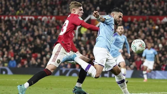 Manchester City's Riyad Mahrez, right, holds off the challenge pf Manchester United's Brandon Williams during the English League Cup semifinal first leg soccer match between Manchester United and Manchester City and at Old Trafford, Manchester, England, Tuesday, Jan. 7, 2020. (AP Photo/Jon Super)